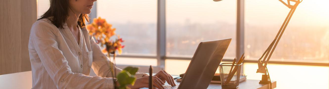 une femme écrit un message depuis son ordinateur