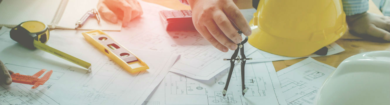 Une personne utilise un compas pour travailler sur des plans de constructions
