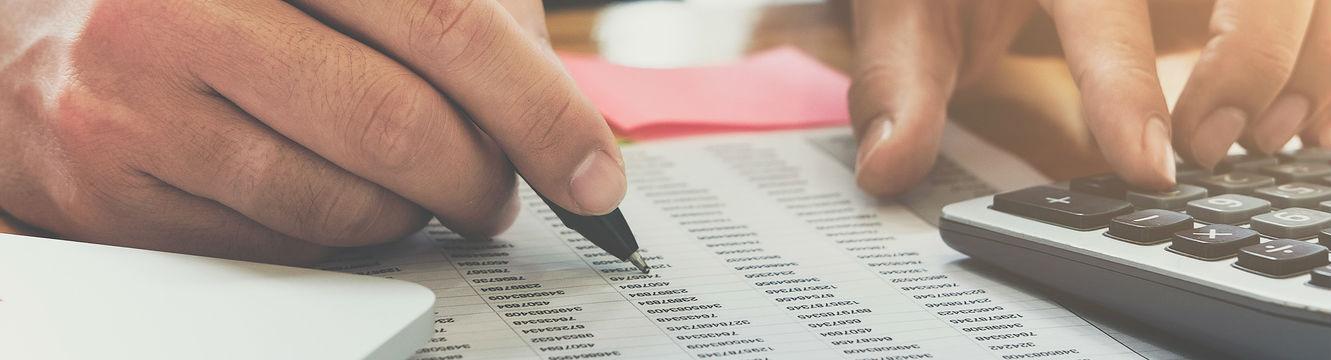 Une personne effectue des calculs à l'aide d'une calculatrice et d'un stylo